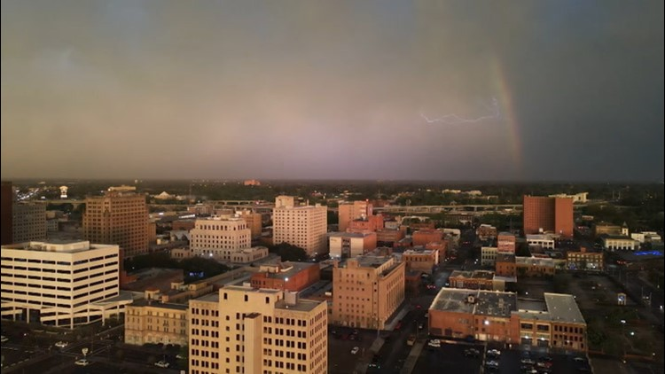 Lightning streaks across the sky behind a rainbow