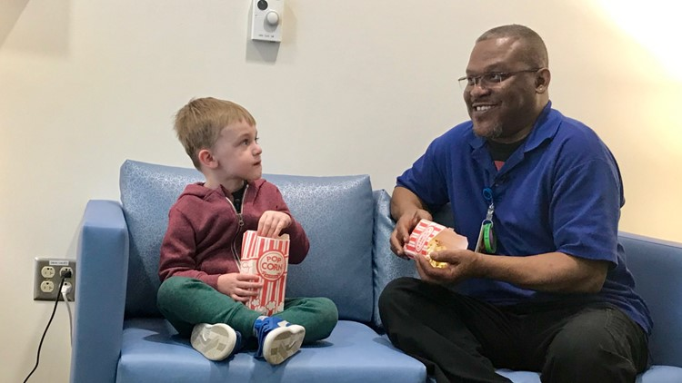 Four-year-old Cooper Baltzell shares popcorn and conversation with Gregory Watson, his best friend