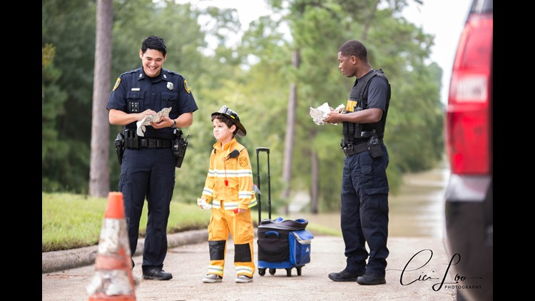 Six-year-old Giovanni delivers breakfast to two Houston police officers helping rescue people flooded in a Kingwood neighborhood.