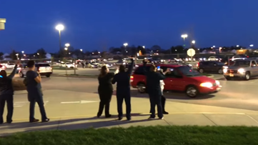Hundreds of cars honk and flash their lights to show support for health care workers