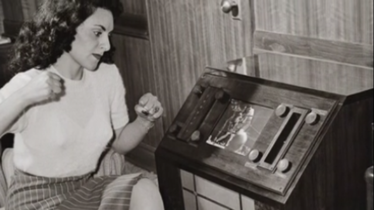 A woman watches boxing on a first-generation TV set.