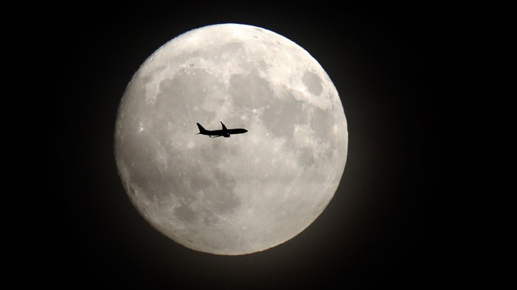 A commerical jet flies in front of the moon on its approach to Heathrow airport in west London on November 13, 2016.