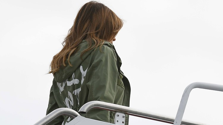 US First Lady Melania Trump boards a flight at Andrews Air Force Base in Maryland on June 12, 2018 wearing a rain jacket that reads : I really dont care. Do U? in white lettering that looks like broad paint strokes.